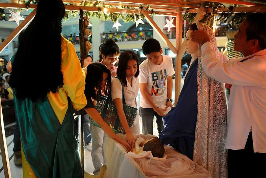 Filipino Christians touch the likeness of Baby Jesus during a Christmas Eve mass at the Saint Peter Parish in Manila on December 24, 2012. The Philippines is Asia's bastion of Catholicism and has the longest known Christmas season in the region beginning with the dawn masses in mid-December until the first week of January. Photo: Noel Celis, AFP/Getty Images