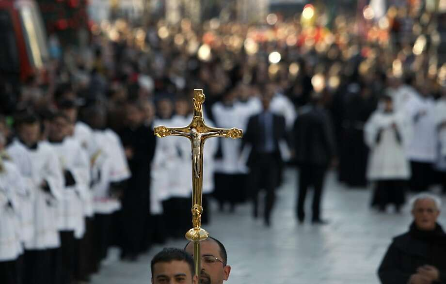 A cross is held during Christmas celebrations outside the Church of Nativity, traditionally believed by Christians to be the birthplace of Jesus Christ, in the West Bank town of Bethlehem, Monday, Dec. 24, 2012. Thousands of Christian worshippers and tourists arrived in Bethlehem on Monday to mark Christmas at the site where many believe Jesus Christ was born. Photo: Adel Hana, Associated Press