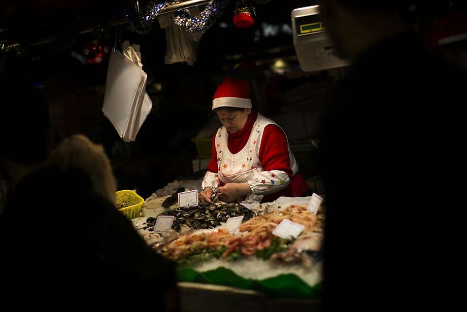 A fishmonger dressed in a festive outfit selects seafood for a client as part of a Christmas dinner in a market in Barcelona, Spain, Monday, Dec. 24, 2012. Retailers remain hopeful for a last-minute burst of Christmas consumerism, and some governments are encouraging it by allowing stores to open on Sunday. But with economies across the region slowing and unemployment soaring, analysts say holiday spending in Europe is bound to disappoint for the fourth year in a row. (AP Photo/Emilio Morenatti) Photo: Emilio Morenatti, Associated Press