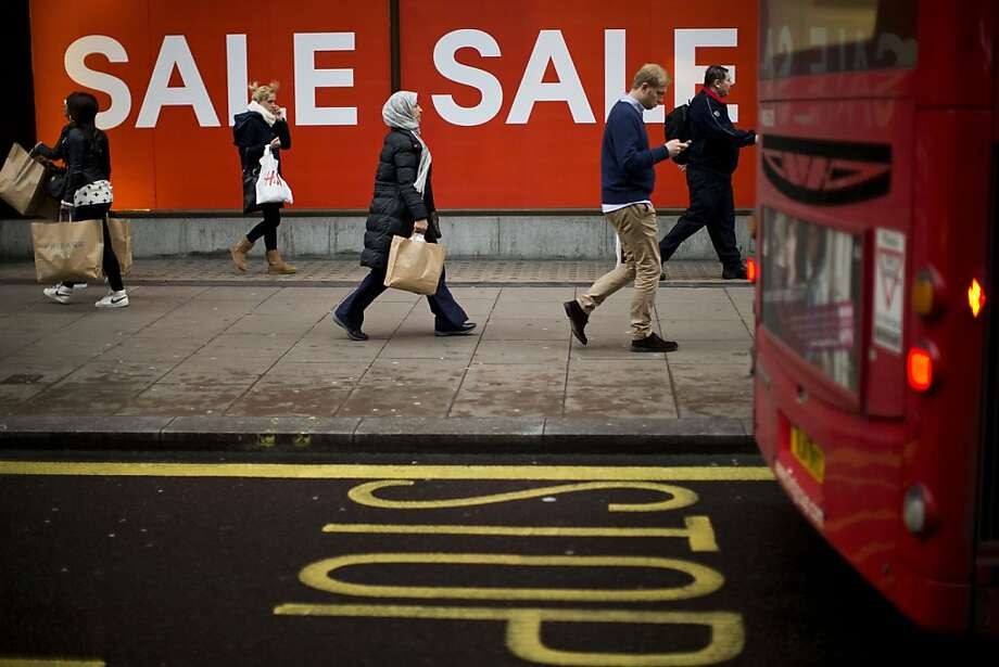 People walk past sale signs on Oxford Street in London, Monday, Dec. 24, 2012. Sales in some UK stores began on Christmas Eve. Photo: Matt Dunham, Associated Press