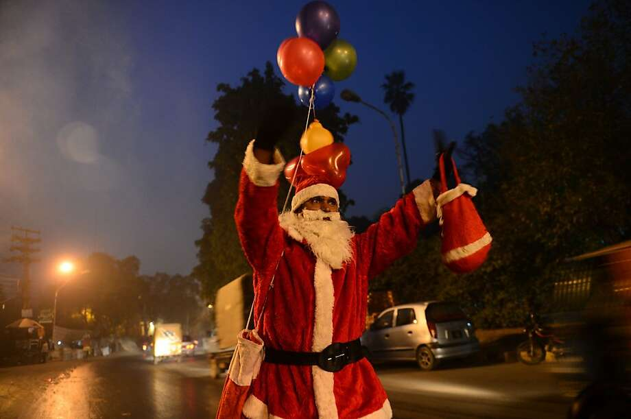 A Pakistani Christian man dressed as Santa Claus walks along a street during Christmas Eve in Lahore on December 24, 2012.  Pakistan is overwhelmingly Muslim and at around two percent of the population, Christians are among the country's most marginalised citizens. Photo: Arif Ali, AFP/Getty Images