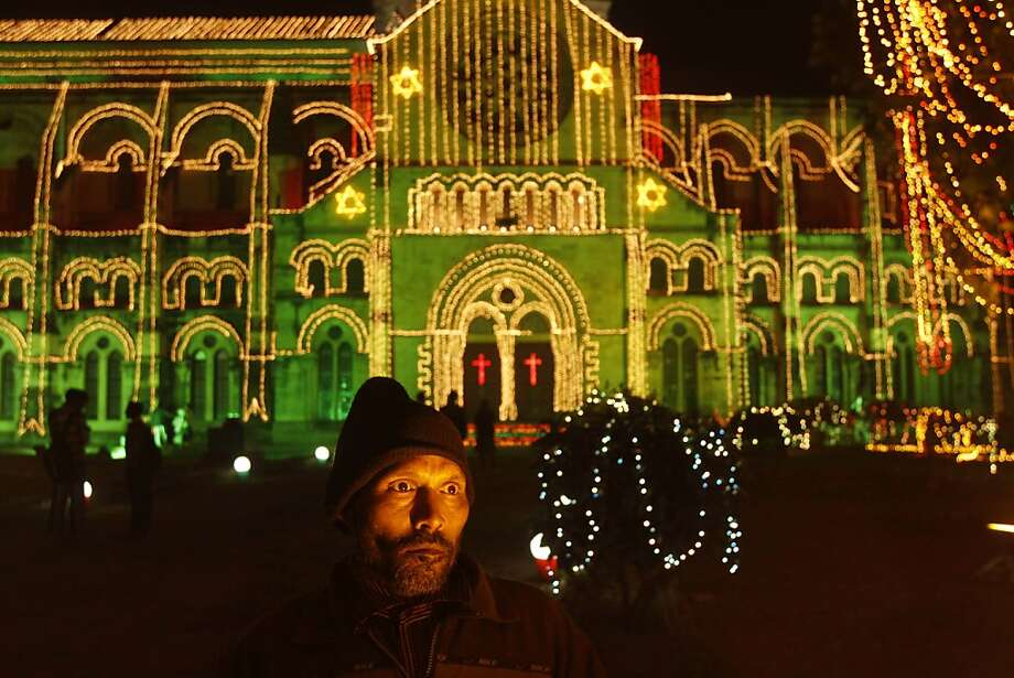 An electrician puts up illuminations at All Saints Cathedral on the eve of Christmas in Allahabad, India, Monday, Dec. 24, 2012. Although Christians comprise only two percent of the population Christmas is a national holiday and is observed across the country as an occasion to celebrate. (AP Photo/Rajesh Kumar Singh) Photo: Rajesh Kumar Singh, Associated Press