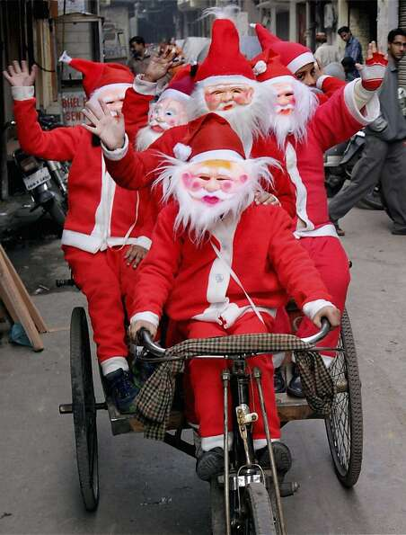 Indian students sporting Santa Claus attire ride a cycle rickshaw to celebrate Christmas in Amritsar
