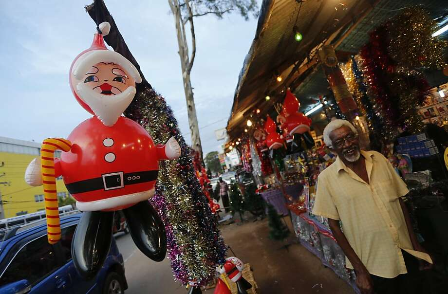A Sri Lankan man reacts to camera as he shops for decorative items on the eve of Christmas in Colombo, Sri Lanka,  Monday, Dec. 24, 2012. Photo: Eranga Jayawardena, Associated Press
