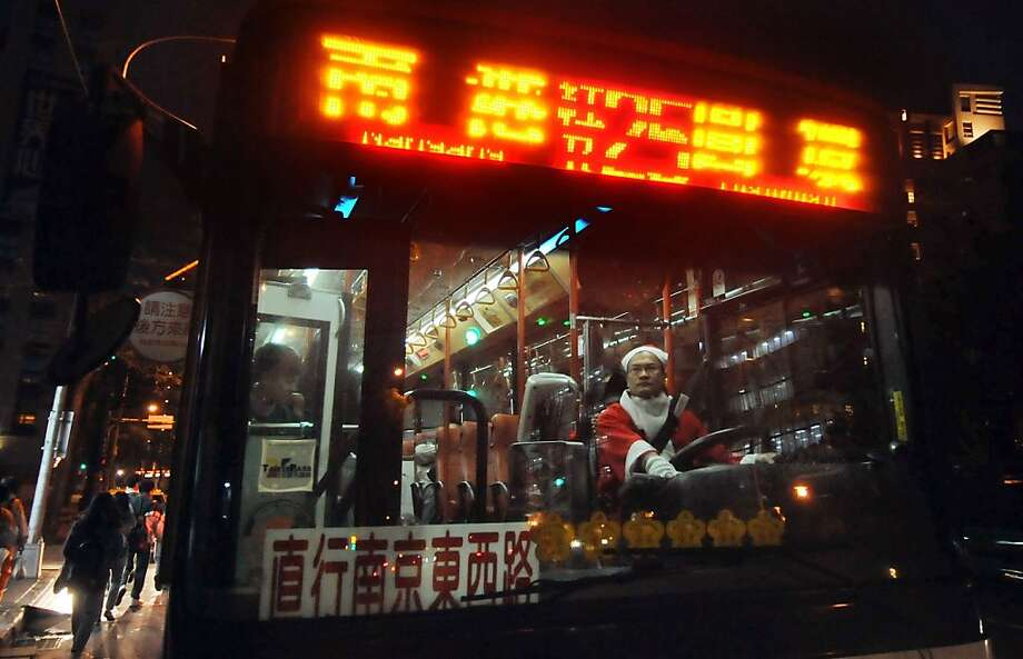A bus driver works dressed in a Christmas themed outfit in Taipei on December 24, 2012. The driver was taking part in a campaign to celebrate the upcoming Christmas. AFP PHOTO / Mandy CHENGMandy Cheng/AFP/Getty Images Photo: Mandy Cheng, AFP/Getty Images