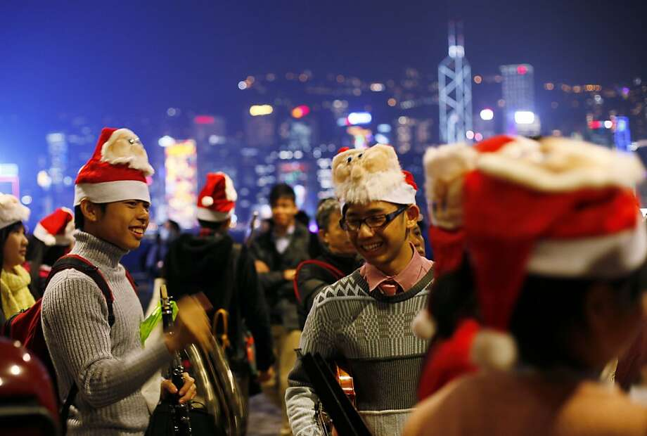 Students play Christmas songs during Christmas eve along the shore of Victoria Harbour in Hong Kong Monday Dec. 24, 2012. Christmas is a public holiday and recognized as commercial event rather than religious event in Hong Kong. Photo: Kin Cheung, Associated Press