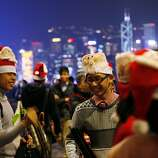Students play Christmas songs during Christmas eve along the shore of Victoria Harbour in Hong Kong Monday Dec. 24, 2012. Christmas is a public holiday and recognized as commercial event rather than religious event in Hong Kong. (AP Photo/Kin Cheung)