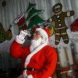 A man dressed as Santa drinks cola as he waits to take part in a Christmas celebration in Mumbai, India, Monday, Dec. 24, 2012. Although Christians comprise only two percent of the population Christmas is a national holiday and is observed across the country as an occasion to celebrate. (AP Photo/Rafiq Maqbool)