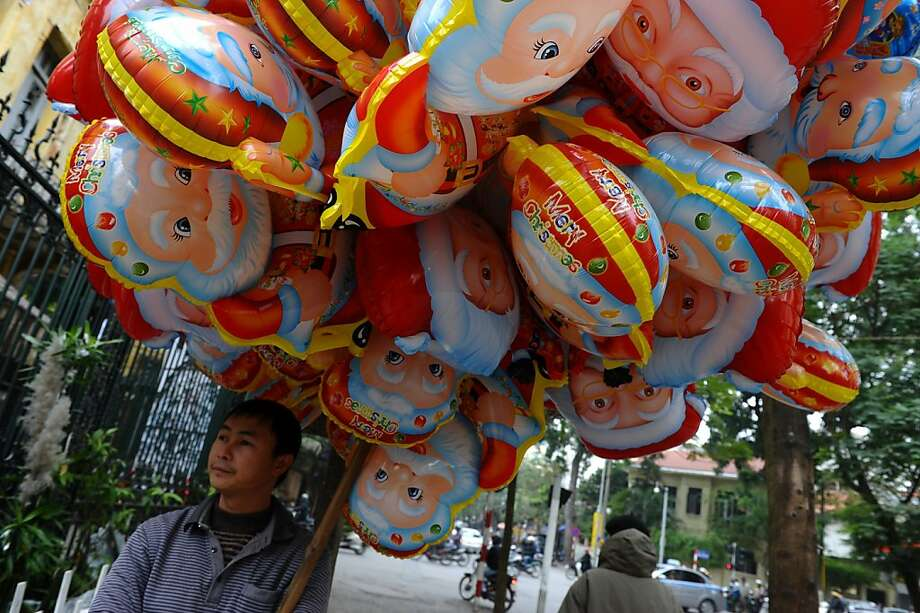 A vendor stands selling Santa Claus balloons outside a church in downtown Hanoi on December 24, 2012. Churches, shops, restaurants and shopping mails are being decorated in the Southeast Asian communist nation where some 6 million catholic community are preparing to celebrate Christmas. Photo: Hoang Dinh Nam, AFP/Getty Images