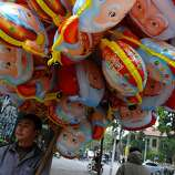 A vendor stands selling Santa Claus balloons outside a church in downtown Hanoi on December 24, 2012. Churches, shops, restaurants and shopping mails are being decorated in the Southeast Asian communist nation where some 6 million catholic community are preparing to celebrate Christmas. AFP PHOTO/HOANG DINH NamHOANG DINH NAM/AFP/Getty Images