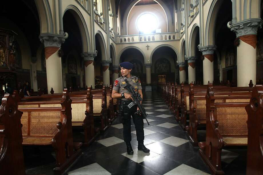"An armed police officer stands guard inside a church during a security sweep ahead of Christmas eve services at the main cathedral in Jakarta, Indonesia, Monday, Dec. 24, 2012. Since the Bali bombings in 2002, the world's largest Muslim country has been battling terrorists who recently operate in small groups and have targeted security forces and local ""infidels"" instead of Westerners. Photo: Tatan Syuflana, Associated Press"