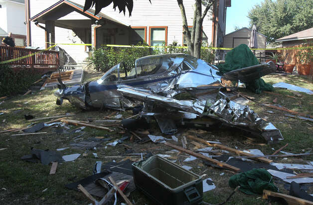 A San Antonio police officer stands by the wreckage of a single engine airplane that crashed shortly after 10 a.m. Monday, Dec. 24, 2012, after taking off from the Twin-Oaks Airport on San Antonio's North Side. According to San Antonio fire captain Bryan Norris, the plane had mechanical problems and hit a fence and landed in the backyard to a home on the 13,000 block of Possum Way. There were two people in the plane and neither of them were hurt. Photo: JOHN DAVENPORT, San Antonio Express-News / ©San Antonio Express-News/Photo Can Be Sold to the Public