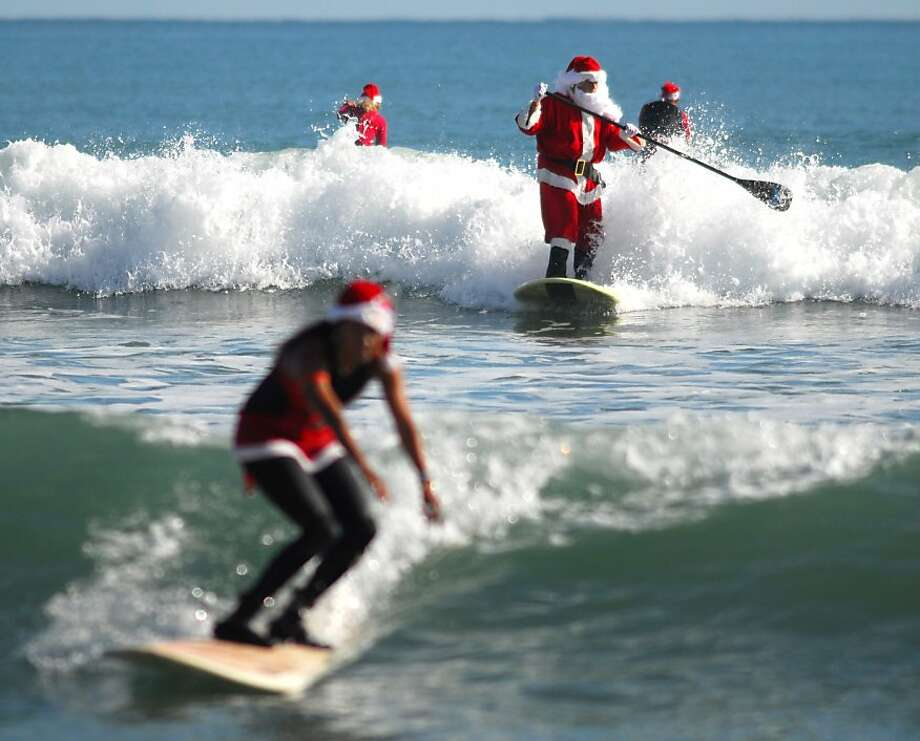 Approximately 150 Surfing Santas, elves, snowmen and other Christmas characters showed up at George Trosset's Surfing Santa event Christmas in the Sand in Cocoa Beach, Fla., Monday, Dec. 24, 2012. The event raised money for Grind for Life, which helps people with cancer. The ocean was filled with Surfing Santas:, men, women, boys and girls. Photo: Malcolm Denemark, Associated Press