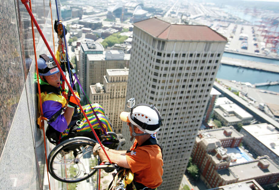 """August 12, 2012— Dale Doornek, a paraplegic from Sultan, Washington, rappels off of Seattle's 1000 2nd Avenue Building during the Special Olympics """"Over The Edge"""" event. Participants raised money for the Special Olympics while rappelling 40 stories off of a building. Photo: SOFIA JARAMILLO / SEATTLEPI.COM"""