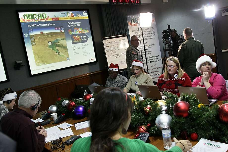 Volunteers take phone calls from children asking where Santa is and when he will deliver presents to their house, during the annual NORAD Tracks Santa Operation, at the North American Aerospace Defense Command, or NORAD, at Peterson Air Force Base, in Colorado Springs, Colo., Monday Dec. 24, 2012. Over a thousand volunteers at NORAD handle more than 100,000 thousand phone calls from children around the world every Christmas Eve, with NORAD continually projecting Santa's supposed progress delivering presents. Photo: Brennan Linsley, Associated Press