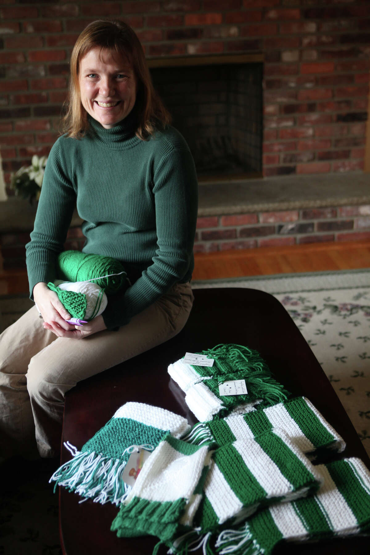 Jeanne Malgiogo, a Trumbull school teacher, sits in her Monroe, Conn. home with scarves that she and others have knitted for the children of Sandy Hook on Monday, December 24 2012. Knitters from all over have joined to help.
