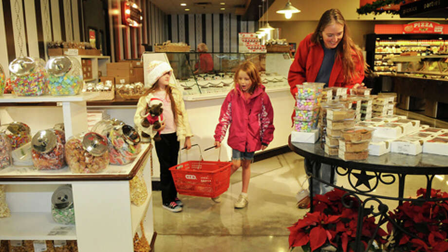 Jenny Coats, 8, from left, Jacelyn Dilby, 7, and Jenny's mom, Kirsten, of The Woodlands, check out one of the displays at the See's Candies shop at H-E-B Woodlands Market. Photo: Jerry Baker, . / Freelance