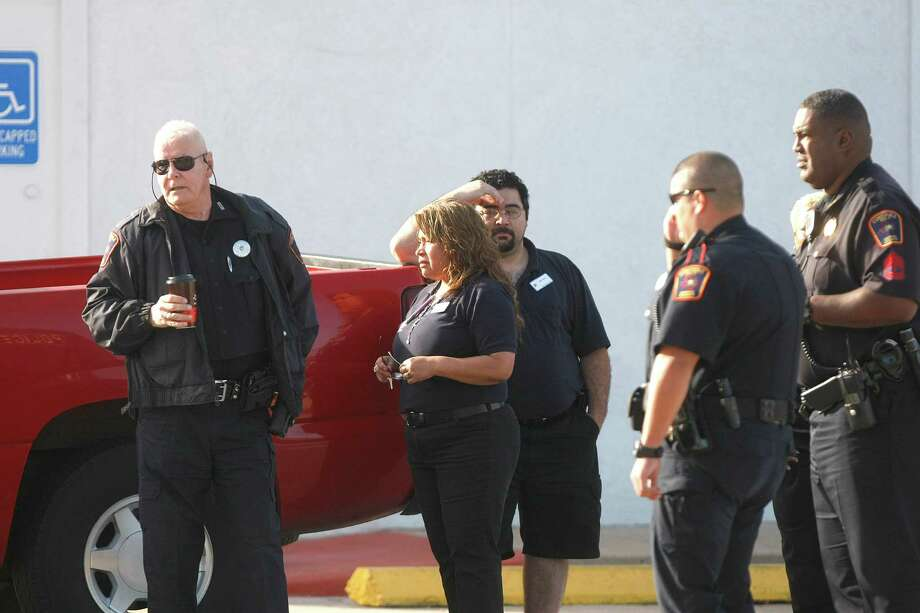 Bystanders look on as police investigate the crime scene on the 5600 block of Bellaire Blvd. where a Bellaire police officer and a bystander were shot to death after a motorist opened fire following a traffic stop Monday morning Monday, Dec. 24, 2012, in Houston. 