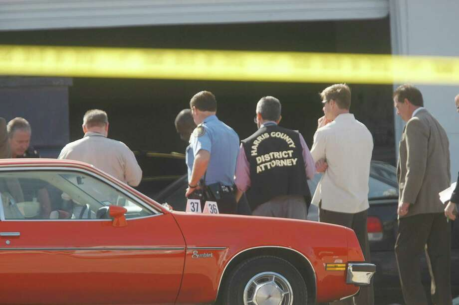 Police investigate the crime scene on the 5600 block of Bellaire Blvd. where a Bellaire police officer and a bystander were shot to death after a motorist opened fire following a traffic stop Monday morning Monday, Dec. 24, 2012, in Houston. 
