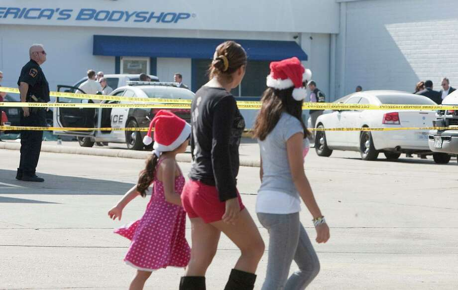 Sarai Rojas. center. walks with her daughters Kimberly Gonzalez, 11, and  Josselyn Rojas, 5, past crime tape as police investigate the crime scene on the 5600 block of Bellaire Blvd. where a Bellaire police officer and a bystander were shot to death after a motorist opened fire following a traffic stop Monday morning Monday, Dec. 24, 2012, in Houston. 