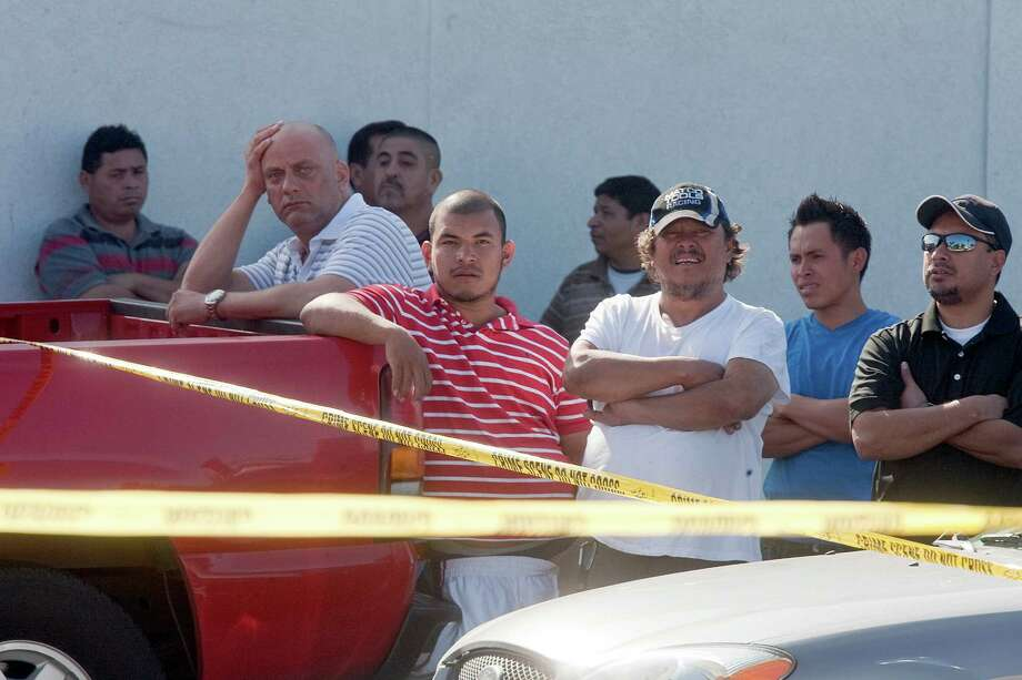 People look on as police investigate the crime scene on the 5600 block of Bellaire Blvd. where a Bellaire police officer and a bystander were shot to death after a motorist opened fire following a traffic stop Monday morning Monday, Dec. 24, 2012, in Houston. 