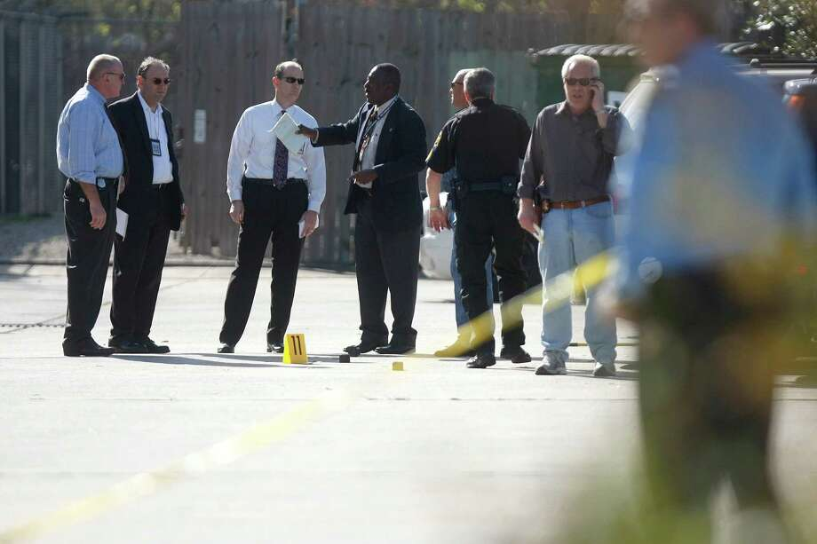 Police investigate the crime scene on the 5600 block of Bellaire Blvd. where a Bellaire police officer and a bystander were shot to death after a motorist opened fire following a traffic stop Monday morning Monday, Dec. 24, 2012, in Houston.  The suspected gunman was wounded. Photo: Johnny Hanson, Houston Chronicle / © 2012  Houston Chronicle