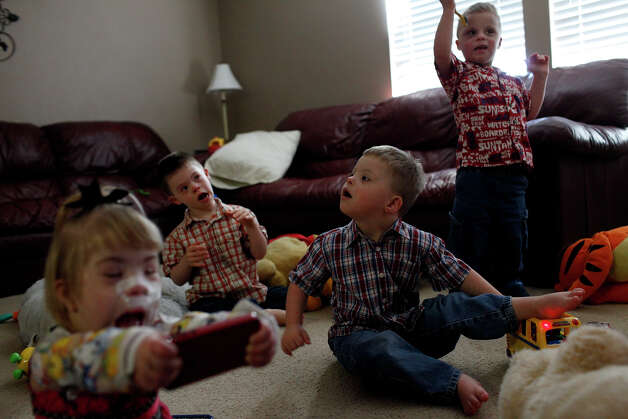 Maclayne Barnett, 4, (from left) with her adopted siblings, Silas, 4, Trenton, 4, and Teague, 5, play at their home in San Antonio on Dec. 18, 2012. Maclayne, Trenton and Teague were all adopted from an orphanage in Eastern Europe while Silas was born in Texas. Photo: Lisa Krantz, San Antonio Express-News / © 2012 San Antonio Express-News