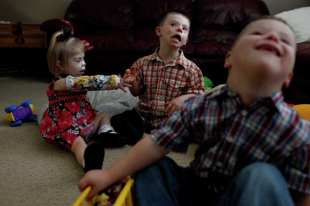 Maclayne Barnett, 4, (from left) plays with her adopted siblings, Silas, 4, and Trenton, 4, as they watch a cartoon at their home in San Antonio on Dec. 18, 2012. Maclayne and Trenton were adopted from the same orphanage in Eastern Europe while Silas was adopted in Texas. Photo: Lisa Krantz, San Antonio Express-News / © 2012 San Antonio Express-News