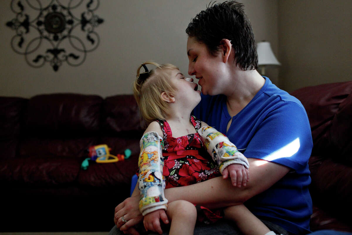 Stephanie Barnett holds her adopted daughter, Maclayne, 4, who has Down syndrome and was born with fetal alcohol syndrome, at their home in San Antonio on Dec. 18, 2012.