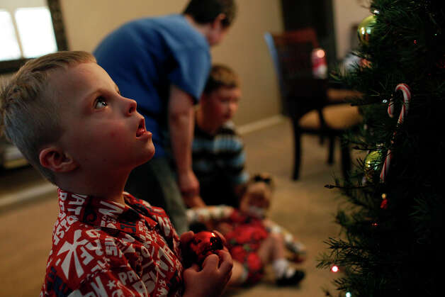 Teague Barnett, 5, looks for a place on their Christmas tree to hang an ornament while his adoptive mother, Stephanie Barnett talks with her other adopted children, Copeland, 10, and Maclayne, 4, as they decorated the tree at their home in San Antonio on Dec. 18, 2012. Photo: Lisa Krantz, San Antonio Express-News / © 2012 San Antonio Express-News