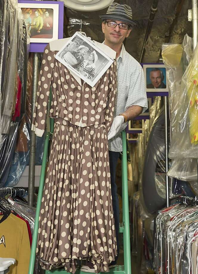 James Comisar shows a dress worn by Lucille Ball, an item in his collection of television memorabilia. Photo: Damian Dovarganes, Associated Press
