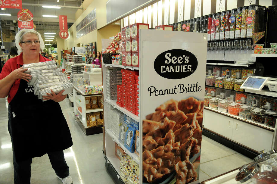 Judith Andersen stocks the shelves at the See's Candies shop at H-E-B Woodlands Market. Photo: Jerry Baker, For The Chronicle / Freelance