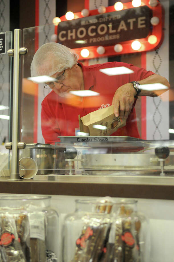 Candy Shop assistant Joe Akers works the See's Candies shop at the H-E-B  Woodlands Market. Photo: Jerry Baker, For The Chronicle / Freelance