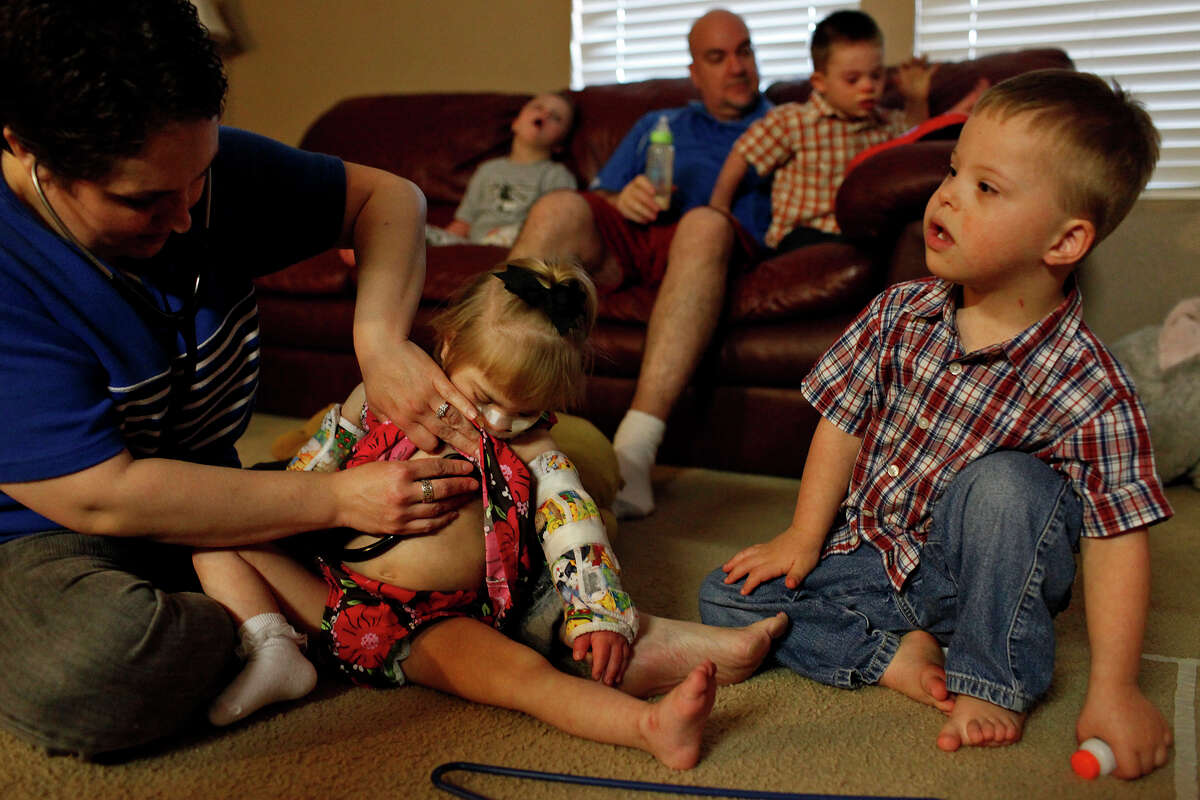 Stephanie Barnett listens to the digestive sounds in Maclayne's stomach after she was fed through a feeding tube while Trenton, 4, (far right) sits next to them. David Barnett sits with with their other adopted children, Teague, 5, and Silas, 4, (right) at their home in San Antonio on Dec. 18, 2012. Barnett listens to the sounds to make sure Maclayne'a stomach is full enough.