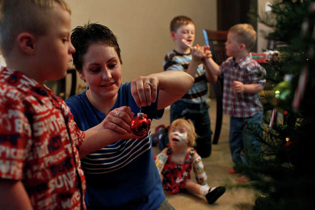 Stephanie Barnett helps her adopted son, Teague, 5, hang an ornament on their Christmas tree while Copeland, 10, Trenton, 4, and Maclayne, 4, wait their turn at their home in San Antonio on Dec. 18, 2012. Photo: Lisa Krantz, San Antonio Express-News / © 2012 San Antonio Express-News