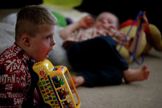 Teague Barnett, 5, (left) and Silas, 4, play and watch a cartoon after school at their home in San Antonio on Dec. 18, 2012. Usually one of the most active of their children, Silas was suffering from a bad cold and stayed home from school. Photo: Lisa Krantz, San Antonio Express-News / © 2012 San Antonio Express-News