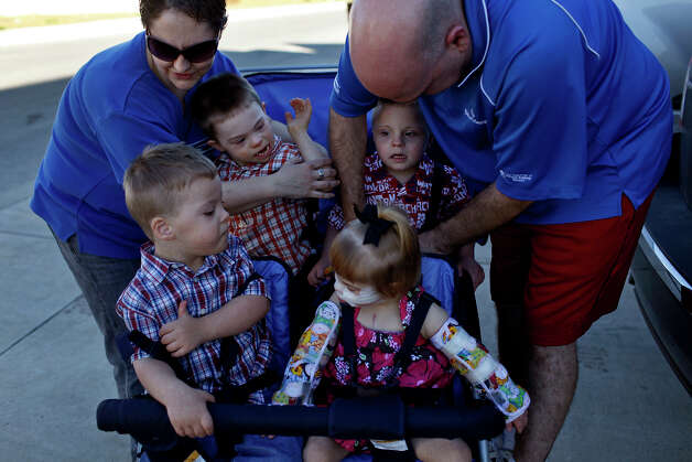 Stephanie and David Barnett strap their adopted children, Trenton, 4 (from left), Silas, 4, Teague, 5, and Maclayne, 4,  into their stroller for a walk around their neighborhood in San Antonio on Dec. 18, 2012. Photo: Lisa Krantz, San Antonio Express-News / © 2012 San Antonio Express-News