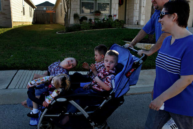 Stephanie and David Barnett take their adopted children, Trenton, 4, (from left) Maclayne, 4, Silas, 4, and Teague, 5, for a walk around their neighborhood in San Antonio on Dec. 18, 2012. Photo: Lisa Krantz, San Antonio Express-News / © 2012 San Antonio Express-News