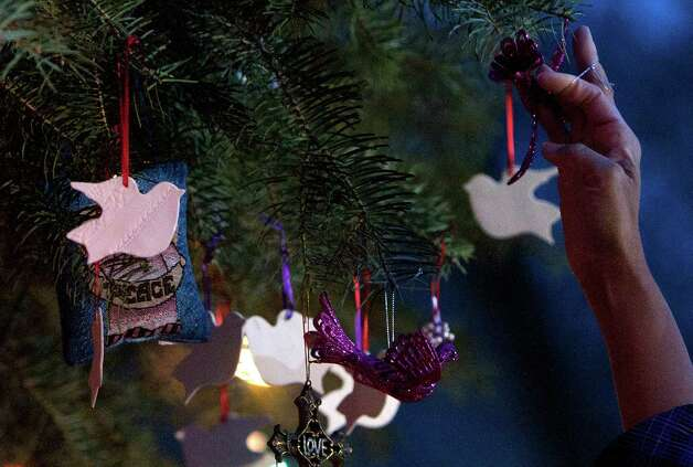 A woman hangs a decoration from a Christmas tree at a memorial site Thursday, December 20, 2012 in Newtown, Conn., honoring the 26 individuals who were killed during a shooting at Sandy Hook Elementary School last Friday. The school was evacuated after Adam Lanza opened fire killing 26 individuals, 20 whom were children. Photo: Cody Duty, Cody Duty/Hearst Newspapers / The News-Times
