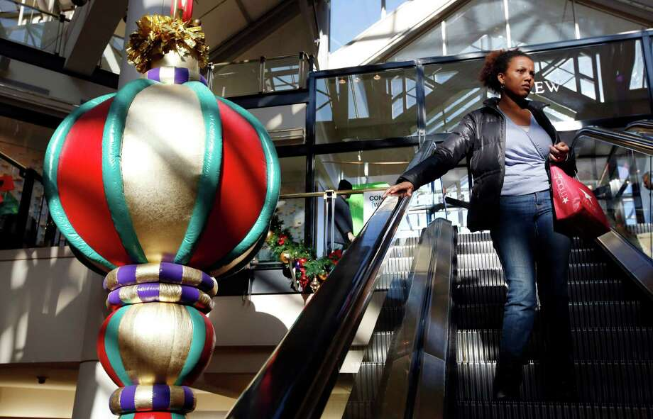 "A woman rides the escalator past a giant holiday ornament at the CambridgeSide Galleria mall in Cambridge, Mass., Monday, Dec. 24, 2012. Although fresh data on the holiday shopping season is expected in coming days, early figures point to a ho-hum season for retailers despite last-ditch efforts to lure shoppers over the final weekend before Christmas. And with concerns about the economy and the looming ""fiscal cliff"" weighing on the minds of already cautious shoppers, analyst say stores will need to offer ""once in a lifetime"" blowouts to clear out inventory.  (AP Photo/Michael Dwyer) Photo: Michael Dwyer, Associated Press / AP"