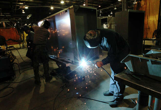 Workers tig-weld the steel pieces to a wardrobe closet at KLN Steel Products on Thursday, Dec. 13, 2012. KLN marked their sixth-month anniversary since it was acquired from bankruptcy by Dallas-based Avteq Inc. The company makes furniture for military barracks and college dorms. Photo: Kin Man Hui, San Antonio Express-News / © 2012 San Antonio Express-News