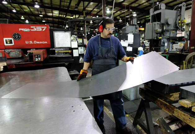 A worker moves off a sheet of steel after being pressed at KLN Steel Products on Thursday, Dec. 13, 2012. KLN marked their sixth-month anniversary since it was acquired from bankruptcy by Dallas-based Avteq Inc. The company makes furniture for military barracks and college dorms. Photo: Kin Man Hui, San Antonio Express-News / © 2012 San Antonio Express-News