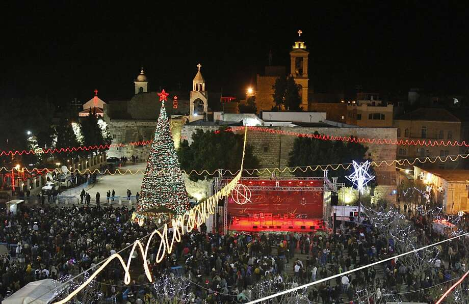 Christian worshippers and tourists celebrate at the Manger Square in front of the Church of the Nativity, in the West Bank town of Bethlehem, Monday, Dec. 24, 2012. Thousands of Christian worshippers and tourists arrived in Bethlehem on Monday to mark Christmas at the site where many believe Jesus Christ was born. (AP Photo/Adel Hana) Photo: Adel Hana, Associated Press