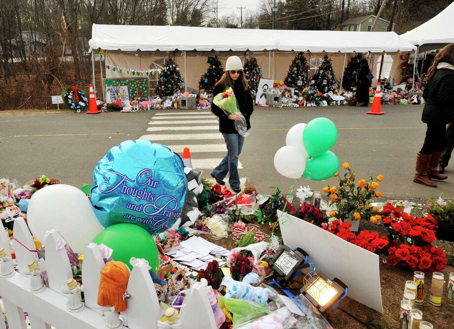 Caroline Burt, of Los Angeles, walks with a bouquet of flowers near the entrance to Sandy Hook Elementary School in Newtown on Monday, Dec. 24, 2012. Photo: Jason Rearick / The News-Times