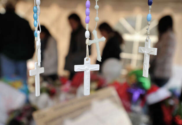 Rosaries hang off a cross among the many makeshift memorials in the downtown Sandy Hook section of Newtown on Monday, Dec. 24, 2012. Photo: Jason Rearick / The News-Times