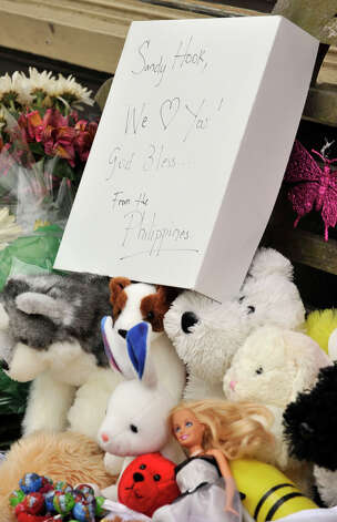 "A makeshift memorial occupies a bench in front of a business in the Sandy Hook section of Newtown on Monday, Dec. 24, 2012. The sign reads, ""Sandy Hook, We Love You! God Bless... From the Phillippines"" Photo: Jason Rearick / The News-Times"