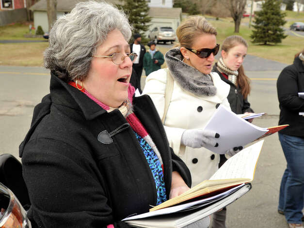 Stacey Severn, left, and Stephanie Debartolomeo sing with other carolers in front of the volunteer firehouse near the entrance to Sandy Hook Elementary School on Monday, Dec. 24, 2012. Photo: Jason Rearick / The News-Times