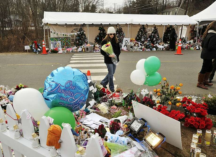 Caroline Burt of Los Angeles, on a holiday trip home to Meriden, Conn., is one of many mourners who have felt compelled to visit the memorial at Sandy Hook Elementary School. Photo: Jason Rearick