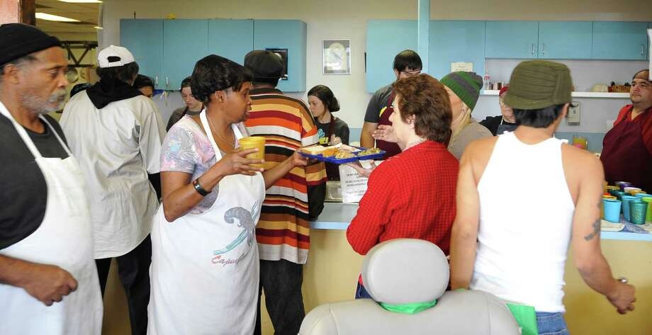 Volunteer Connie Oliver, center, carries a tray to a guest needing assistance. The Hospitality Center daily meal site in Port Arthur, operated by Catholic Charities of Southeast Texas, first opened its doors to feed the hungry on Christmas Day,1987, making this Christmas Day the Center's 25th anniversary. The center is located on Gulfway Drive in Port Arthur and provides a midday meal to the poor 365 days of the year, serving over 40,000 meals.  Dave Ryan/The Enterprise Photo: Dave Ryan
