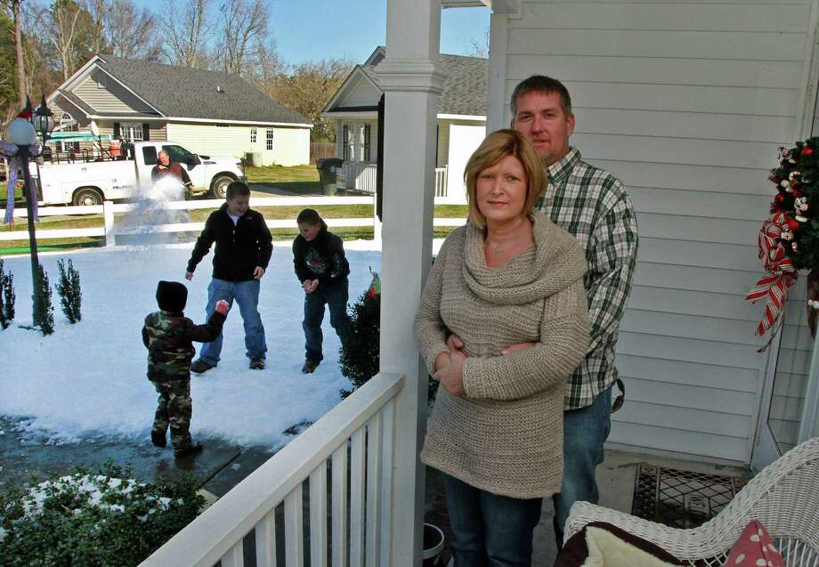 Laurie and Kevin Pearson stand on the porch of their home in Wilson, N.C., while visiting family play in their snow-covered yard. Laurie, who is battling stage-four cancer, said she wished to see snow covering the couple's yard for Christmas. When she returned from the hospital Saturday after a treatment, she found that Kevin had arranged with a snow blowing service to have four tons of snow blown on the couple's yard. Photo: Gray Whitley, Associated Press / The Wilson Times